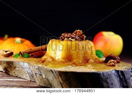pumpkin-Apple pudding with honey,cinnamon and walnuts on wooden Board