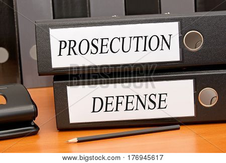 Prosecution and Defense - two binders on desk in the office