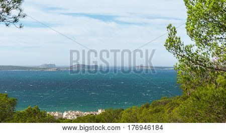 View out to sea and the famous rock islands near Ibiza from the side of the hill nearby in St Antoni de Portmany, Balearic Islands, Spain.