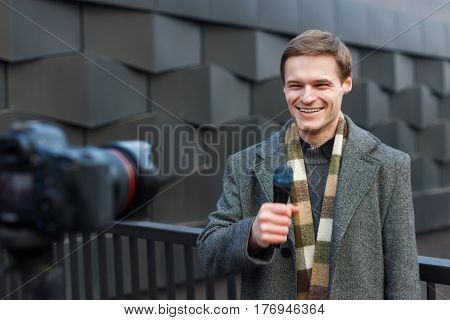 A Happy Male Reporter Leads A Report On The Camera On The Street.