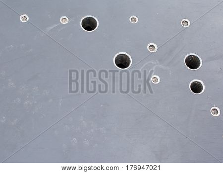 An unusual dark background with holes. Black smooth surface with holes.