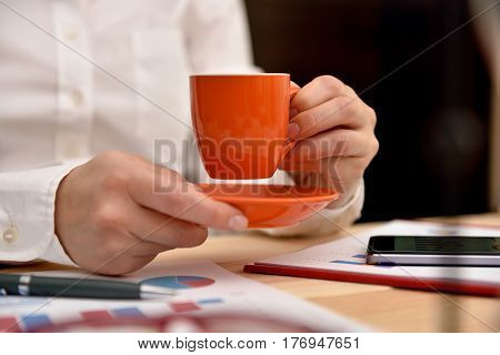 businesswoman with coffee cup and saucer. Tablet with financial data in form of charts and diagrams