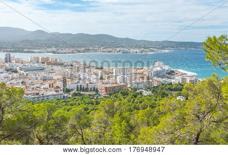 View through naturally framing trees, from hillside of nearby town: San Antonio Sant Antoni de Portmany in the Balearic Islands, Ibiza, Spain.