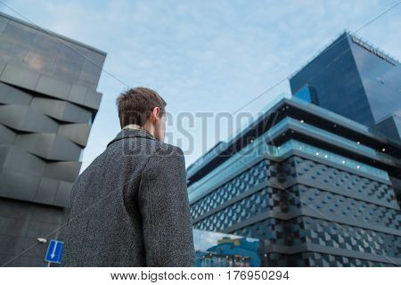Back view of young confident man leader standing near the office building. Bottom view.