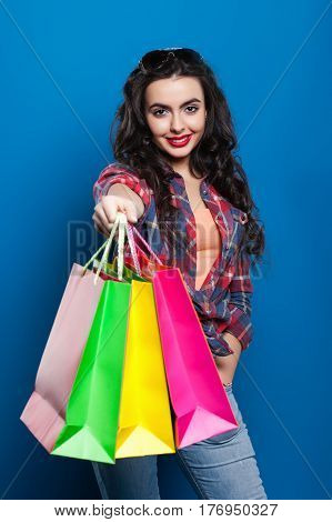 beautiful young girl with red lips smiling on a blue background shows many colorful shopping bags
