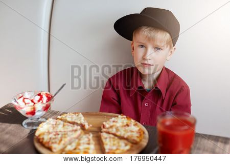 A portrait of stylish little boy dressed in red shirt and modern cap sitting at table in the cafe tasting delicious pizza ice-cream and tomato juice looking directly into camera