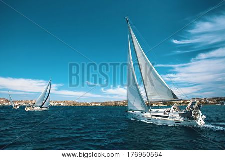 Luxury yachts at regatta. Sailing through the waves at the Aegean Sea.