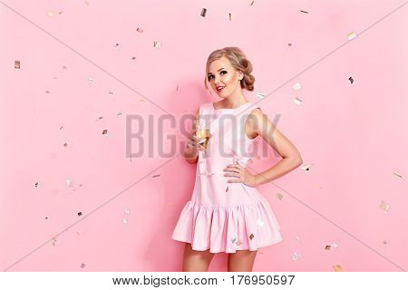 Pretty young woman with a sham glass posing on the pink background. Studio shot.