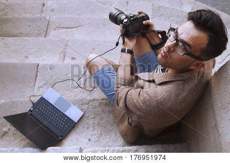 Young photographer viewing his photos on the back of the camera LCD display (Creativity hobbies work freelance concept)