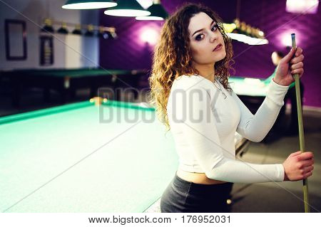 Young Curly Girl Posed Near Billiard Table. Sexy Model At Black Mini Mini Skirt Play Russian Snooker