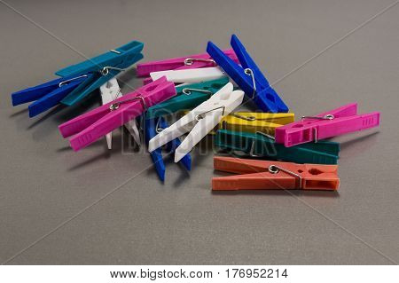 Colorful clothes pegs on a gray background