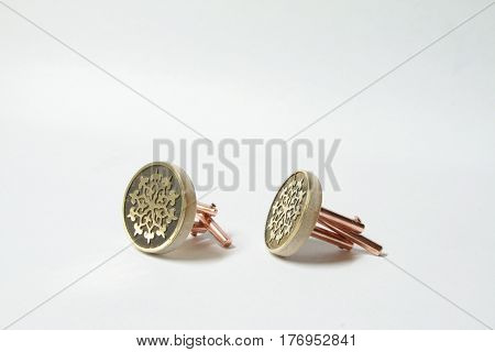 Brass cufflinks on wood base with etching on the top