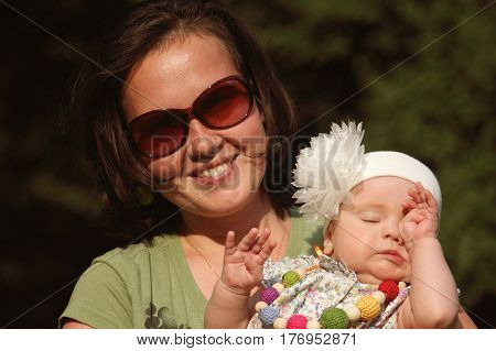 Parents love. Beautiful tired and sleepy baby girl sitting in mom's arms. Happy young mother admires her daughter.