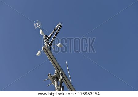 Anemometer or wind vane on a blue sky