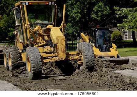 A road grader blades moves earth in a road construction street project