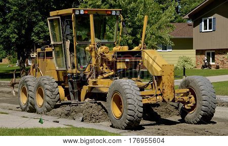 A road grader blades moves earth in a road repair construction street project of a residential neighborhood.