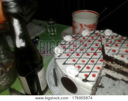 attribute black bottle brandy cake celebration chocolate circles confection constant cream dessert festive holiday liquor piece small sweet table white wine