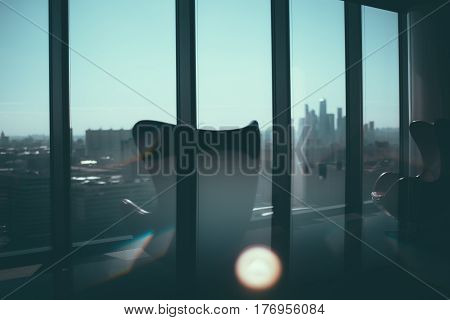 Silhouettes of two empty curved armchairs near each other standing on reflective floor of modern office next to window with cityscape outside and silhouettes of Moscow City business skyscrapers group