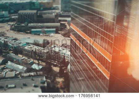 Tilt-shift shooting from high above of skyscraper corner glass facade with two orange stripes on it and multiple houses below with copy space for your advertising text message or promotional content
