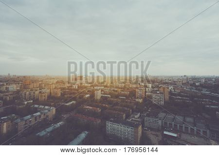 Wide angle view from high above of metropolitan city: multiple residential districts and houses cloudy sky trees and parks industrial zone road hazy horizon on sunset or sunrise