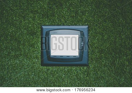 Modern multifunctional climate control device with white blank screen on artificial grass wall mock up of remote control unit on office green wall to operate different devices in recreational zone