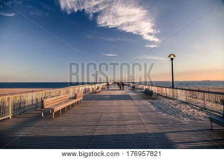 Sun ad clouds over a pier at the Coney Island boardwalk
