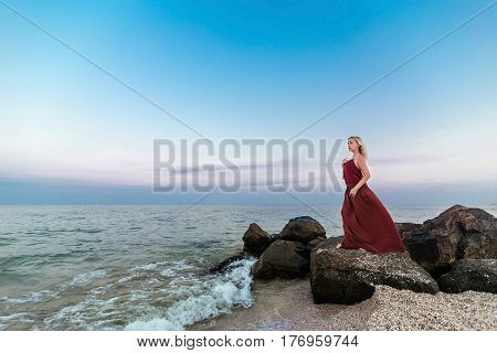Beautiful girl in a claret dress on the sea beach on the rocks