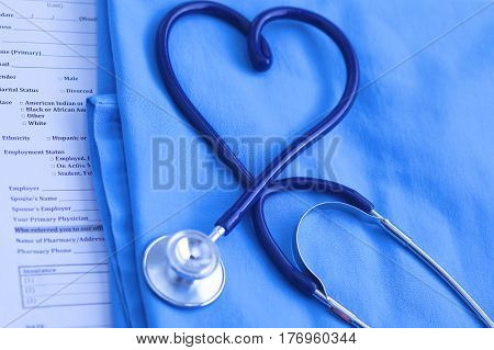 Medical stethoscope twisted in heart shape lying on patient medical history list and blue doctor uniform closeup. Medical help or insurance concept. Cardiology care, health, protection and prevention.