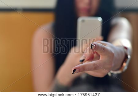 The Brunette Girl Takes Pictures Of Her Two Fingers On A Modern Touch Smartphone