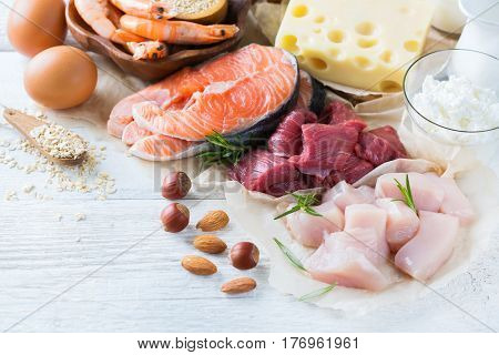 Assortment of healthy protein source and body building food. Meat beef salmon shrimp chicken eggs dairy products milk cheese yogurt beans quinoa nuts oat meal