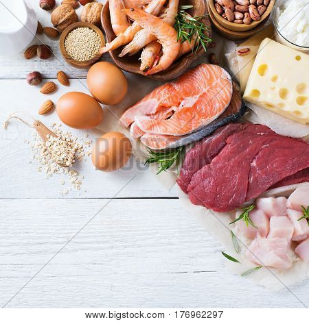 Assortment of healthy protein source and body building food. Meat beef salmon shrimp chicken eggs dairy products milk cheese yogurt beans quinoa nuts oat meal. Top view