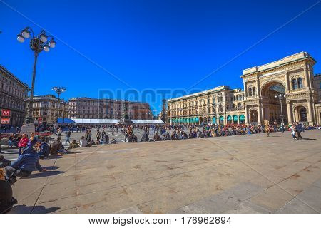 MILAN, ITALY- MARCH 7, 2017: panorama of Piazza Duomo di Milano in a blue sky day. Tourists with the equestrian statue of Vittorio Emanuele II and arcaded mall Vittorio Emanuele II doorway.