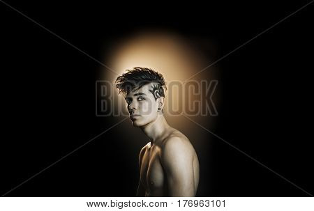 Model man with a hairstyle on a black background
