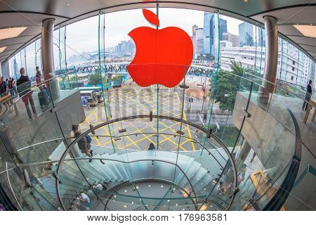 Hong Kong, China - December 4, 2016: fish-eye wide view of Red Apple sign and modern spiral staircase in Apple store, IFC Mall, with Observation Ferris Wheel at Victoria Harbour skyline on background.