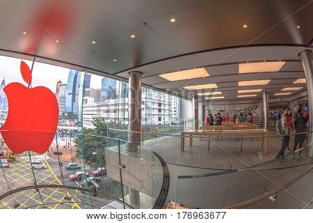 Hong Kong, China - December 4, 2016: Red Apple sign and customers looking the new technological products and shop clerks in red. Apple store, IFC Mall, with Central District skyline on background.