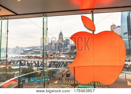 Hong Kong, China - December 4, 2016: close up of Red Apple signboard in Apple store of IFC Mall, Central District skyline outside the crystal glass window. Modern technological city concept.