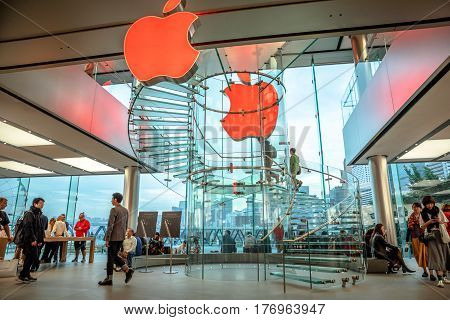 Hong Kong, China - December 4, 2016: two red Apple signboard in IFC Mall store, full of customers looking the new technological products, HK cityscape on background.
