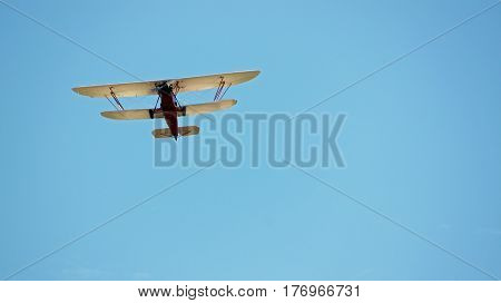 Red and White Biplane Flying in a Blue Sky