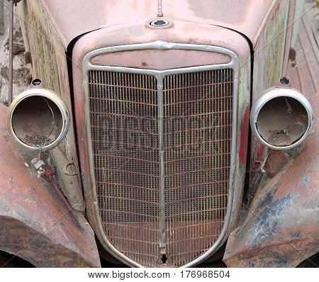 Closeup of a Vintage Car Grill with Headlights Missing