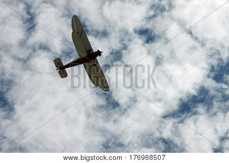 Red and White Biplane in a Blue and White Sky