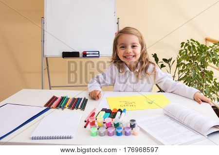 Beautiful little girl with wavy hair draws sitting at table