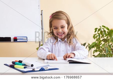 Beautiful little girl with wavy hair reads sitting at table