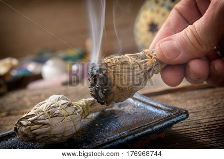 Man's hand with burning natural white sage incense