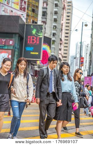 Hong Kong, China - December 6, 2016: A group of friends crosswalking the Yee Wo street, located on the Henessy road of Causeway Bay. An ultimate destiantion for luxury shopping, fashion and travel.