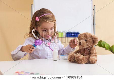 pretty blond Little girl treats a toy bear