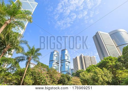Hong Kong cityscape of modern skyscrapers and towers in the Central business district in a sunny day with blue sky seen from the Hong Kong Park, an green oasis of peace.