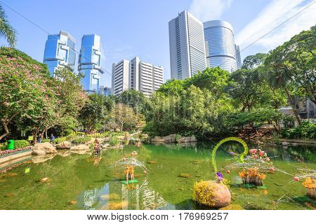 Scenic landscape of the pond at the lush green garden of Hong Kong Park, that reflects the modern skyscrapers and towers in the Central business district. Sunny day with blue sky.