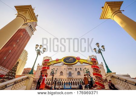 Macau, China - December 9, 2016: People in front of main entrance of The Venetian, the largest casino in the world and the largest single structure hotel building in Asia. Cotai Strip, sunny day.