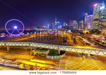 Spectacular aerial view of cityscape in Hong Kong, Central District, with Observation Ferris Wheel at Victoria Harbour illuminated at night.