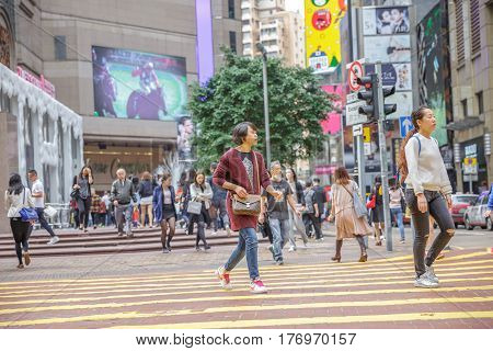 Hong Kong, China - December 6, 2016: Causeway Bay is one of the most attractive areas for tourists and business people and good for shopping. Asian woman crossing the Times Square intersection